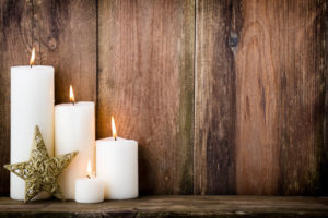 four white christmas candles all lit with a gold star decoration against an attractive wooden backdrop