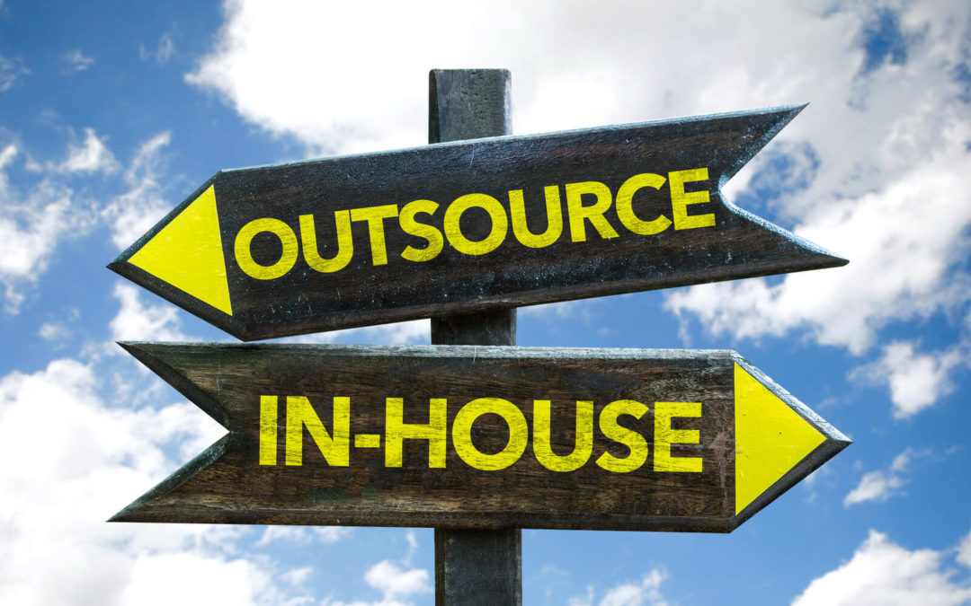 crossroads sign with two directions outsource or in-house